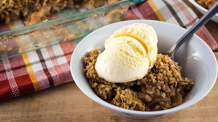 Warm homemade apple crisp served with ice cream in a white bowl.