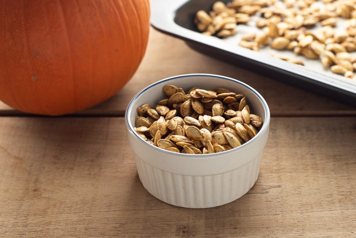 Small bowl of homemade roasted pumpkin seeds on a wooden table next to a pumpkin.