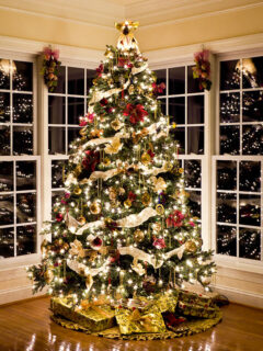 Beautiful real Christmas tree decorated in front of windows.