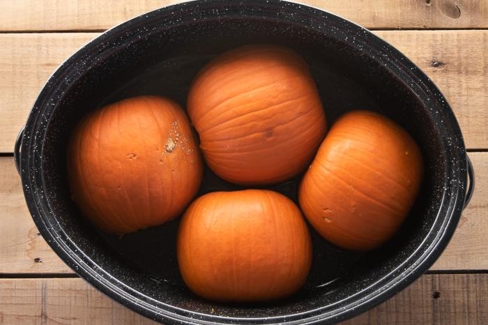 Pie pumpkins cut side down in a roasting pan.
