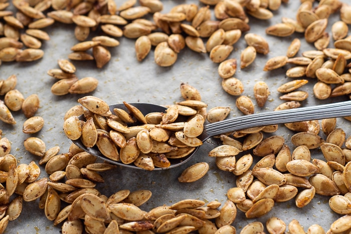 A spoon full of roasted pumpkin seeds on a baking tray.