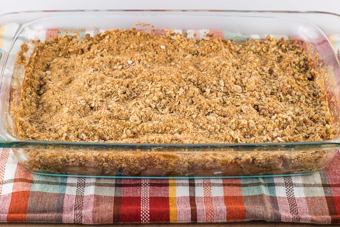 Homemade apple crisp warm out of the oven in a glass baking dish.