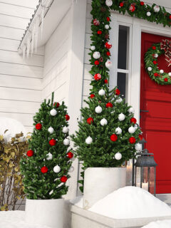 Two fake Christmas trees in containers on a porch.
