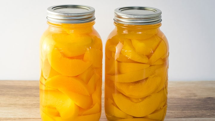 2 jars of home canned peaches on a table.