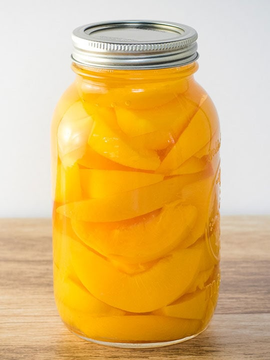 Jar of home canned peaches on a wooden table.