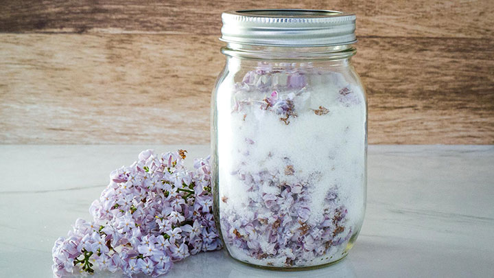 Lilac sugar in a mason jar with purple lilac flowers next to it on the table.