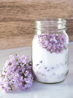 Purple lilac flowers in a jar with white sugar. On the table next to it are more lilac flowers.