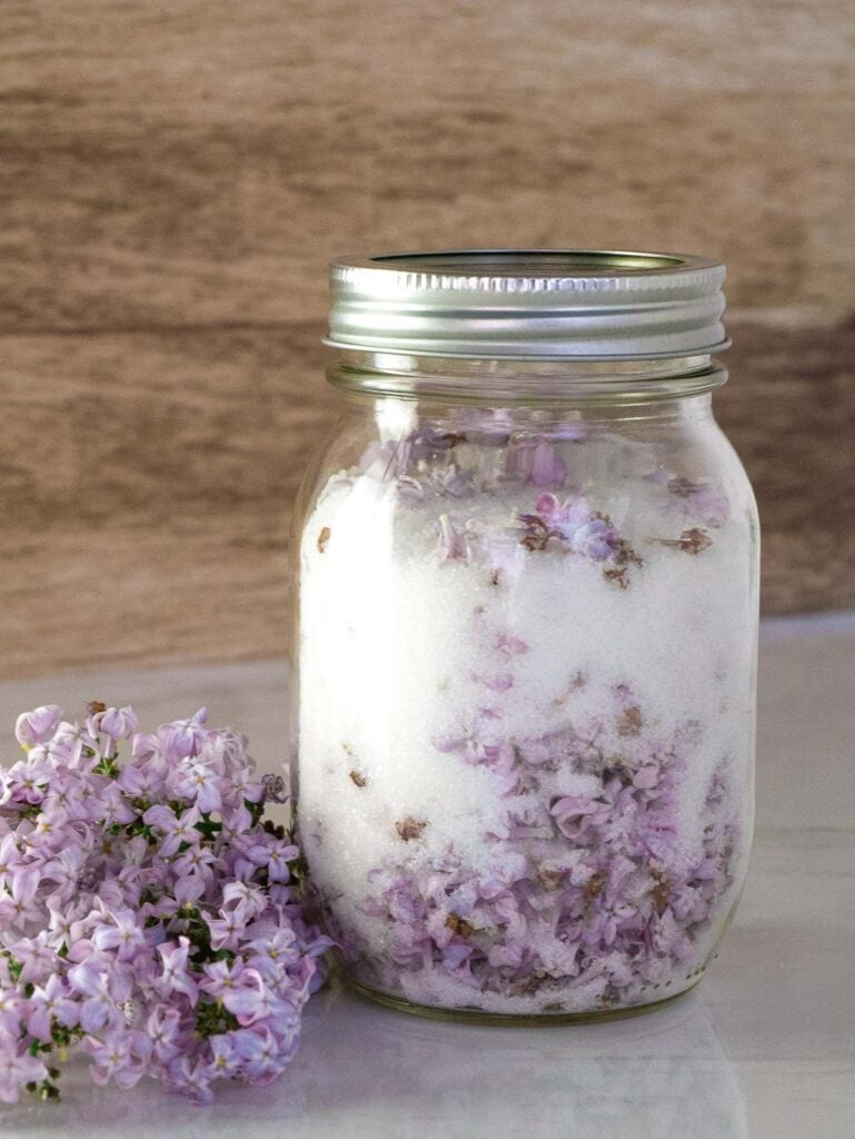 Lilac sugar in a canning jar sitting on a table with flowers next to it.
