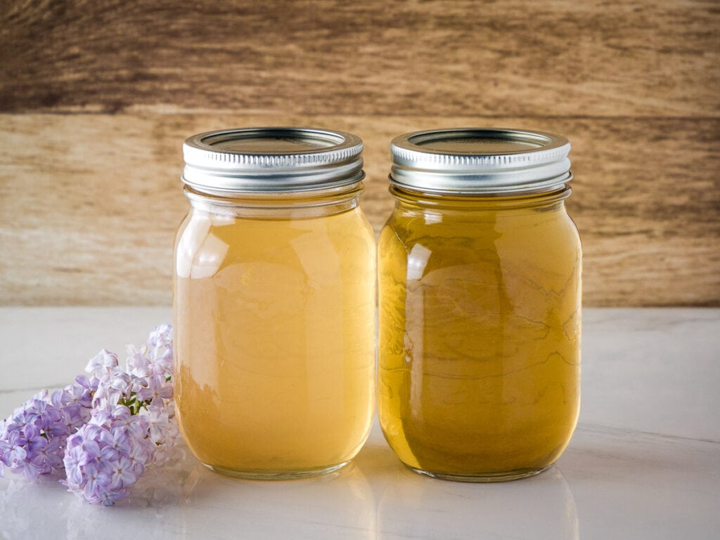 2 jars of lilac syrup one light yellow and the other dark yellow.