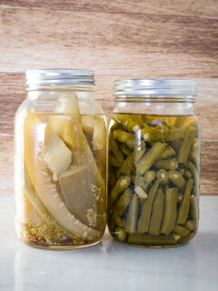 A jar of homemade pickles and green beans on a counter.