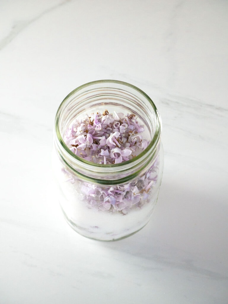 Mason jar filled with purple lilac flowers and white sugar.