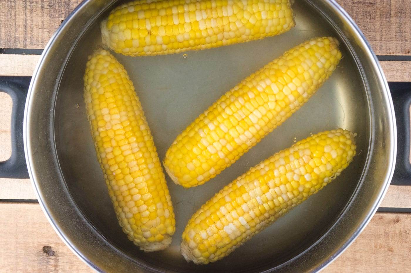4 cobs of corn cooked in a pot.