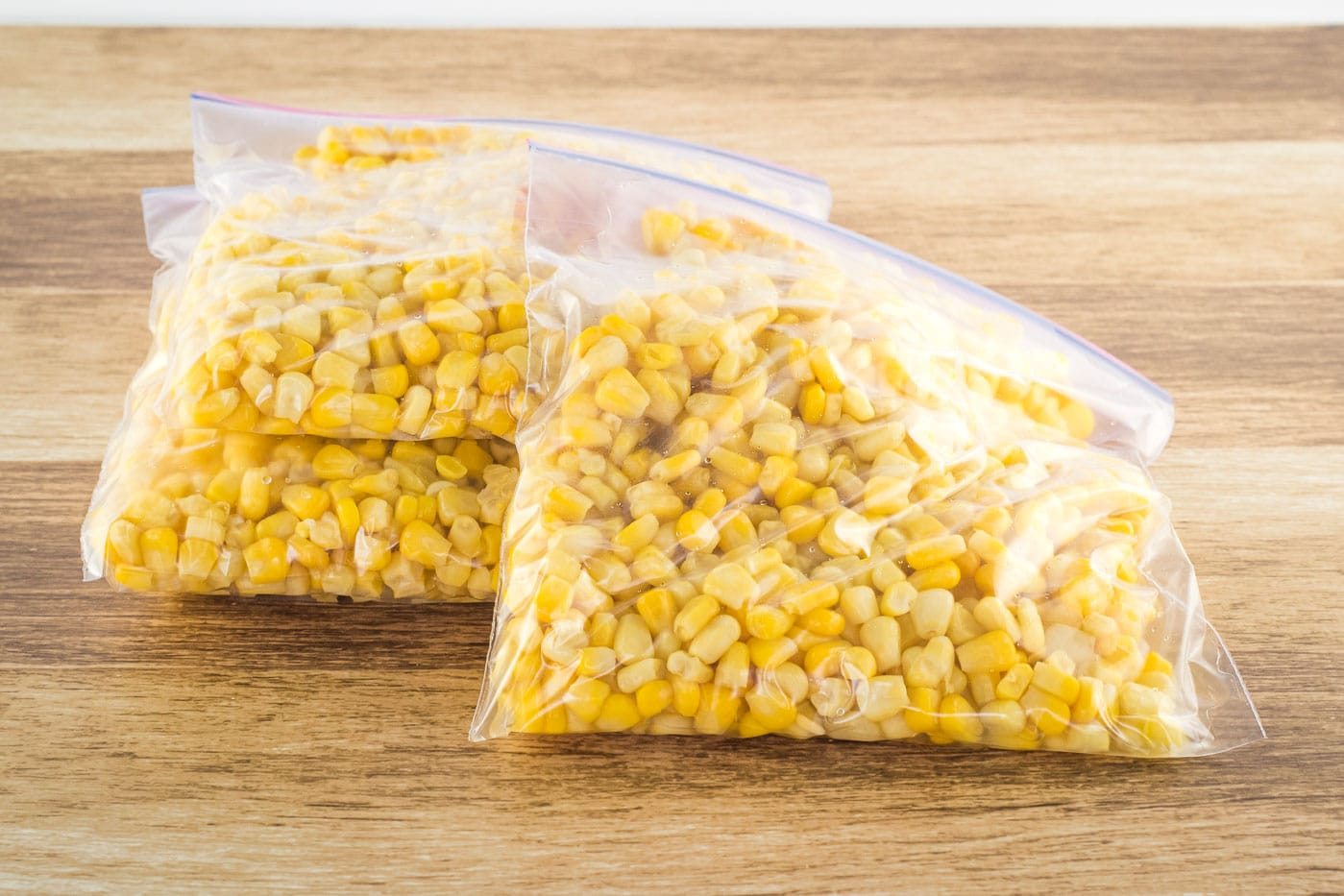 3 Freezer bags filled with corn on a wooden table.