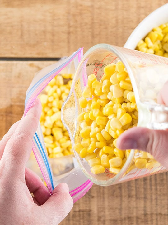 Pouring corn into a freezer bag.