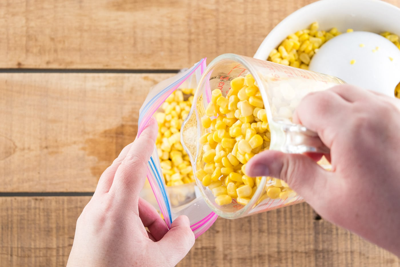 Measuring sweet corn into freezer bags.
